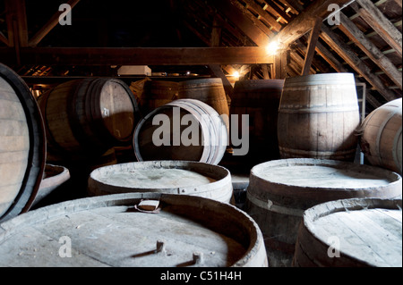 Barrels containing beer stack against each other in the Cantillon brewery in Brussels, Belgium. - Stock Photo