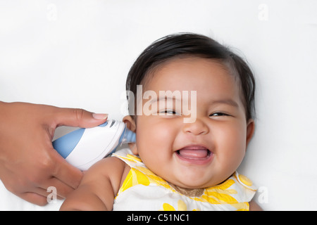 Healthy baby having temperature taken using an infrared ear thermometer - Stock Photo
