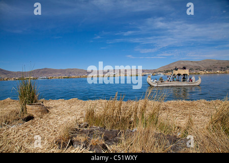 View from one of the floating Uros Islands of tourists being rowed in a traditional reed boat, Lake TIticaca, Peru - Stock Photo