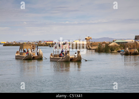 Tourists being rowed in traditional reed boats on Lake Titicaca, Peru - Stock Photo