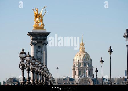 lampadaires et statue du pont Alexandre III, au fond le dôme de l'hotel des Invalides lampposts, statue of Alexander - Stock Photo