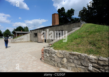 Auschwitz 1 former concentration camp and now a State Museum - A tourist walks past the gas chamber and crematorium - Stock Photo