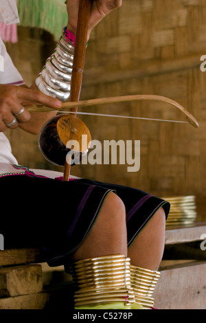 A Karen Paduang woman wearing gold rings on her legs is sitting at her home playing a musical instrument in Northern - Stock Photo
