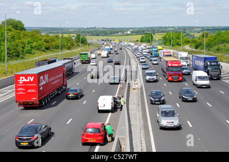 Motorway vehicles stationary in lane 4 accident involving red car below bridge (witnesses awaiting emergency services) - Stock Photo