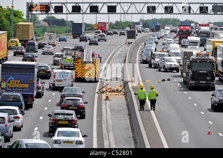 View from above looking down on busy M25 motorway traffic jam emergency services attend to two accidents on both directions fire engine arrives UK