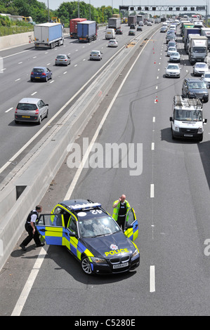 Essex police at  M25 motorway car crash accident under bridge parking in lane 4 with skid marks beyond into concrete - Stock Photo