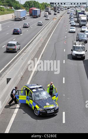 Essex police at  M25 motorway car crash accident under bridge parking in lane 4 with skid marks beyond into concrete - Stock Photo