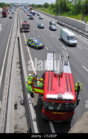 Police car and fire engines arriving at accident scene (under bridge) parking in lane four - Stock Photo