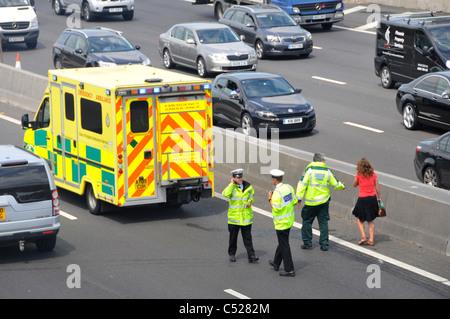 Paramedic escorts woman to waiting ambulance at scene of motorway car crash (under bridge) whilst police check accident - Stock Photo