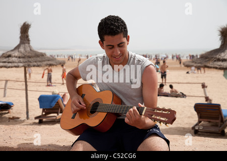 Man plays guitar  on Essaouira beach - Stock Photo