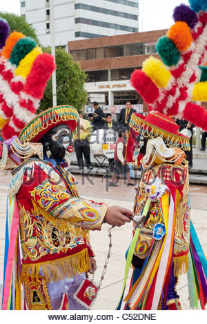 Masked Kapac Negro with large brightly colored headresses and hand-made costumes performing on the Plaza de Armas - Stock Photo