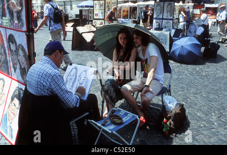 A young couple of tourists sit for a caricature double portrait in Piazza Navona, Rome, Latium, Italy. - Stock Photo