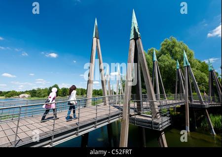 Abstract wooden footbridge crossing lake at Britzer Garden in Neukolln in Berlin Germany - Stock Photo