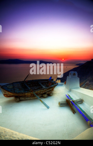 Thira on iconic Greek island of Santorini, typical Greece, old boat on white washed building as sun sets, sunset - Stock Photo