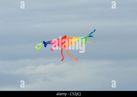Multi-coloured kite flying high in the sky in the UK - Stock Photo