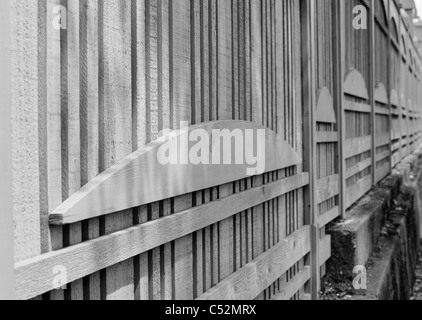 Black and white image of a unique design wood fence in diminishing perspective - Stock Photo