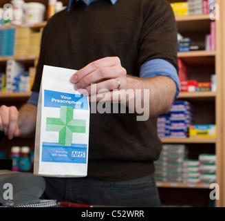 pharmacist handing over prescription at chemist - Stock Photo
