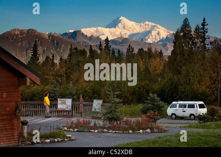 Woman views Mt. Mckinley and Alaska Range from interpretive display along the George Parks Highway, Alaska - Stock Photo