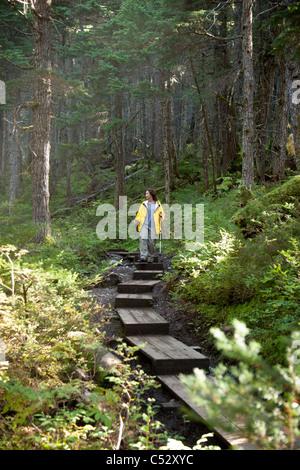 Woman hiking on a boardwalk path along Winner Creek Trail in a boreal rain forest near Girdwood, Chugach National - Stock Photo