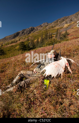 Male moose hunter rests on a sunny mountainside with his trophy moose antler rack in the Chugach National Forest, - Stock Photo