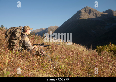 Male moose hunter sits on a hillside and aims with a rifle, Bird Creek area, Chugach National Forest, Alaska - Stock Photo