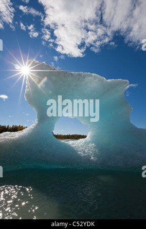 Sunny view of an iceberg in Mendenhall Lake with the sun shining from behind, Southeast Alaska, Summer - Stock Photo