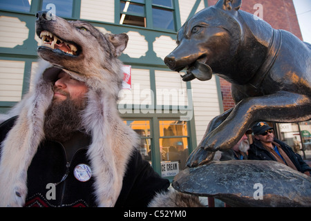 Man wearing a wolf hat stands next to a bronze statue of a sled dog in downtown Anchorage during Fur Rendezvous, - Stock Photo