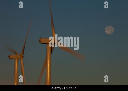 Pillar Mountain Wind Project wind turbines on Pillar Mountain at dawn with a full moon in the background, Kodiak - Stock Photo