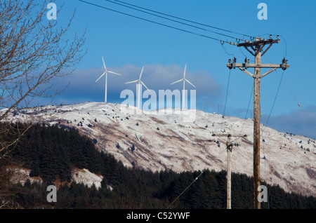 Pillar Mountain Wind Project wind turbines, Kodiak Island with electric poles and lines in the foreground, Alaska - Stock Photo