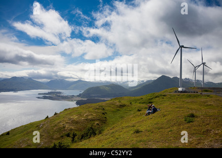 Hikers enjoying a sunny afternoon walk near the wind turbines, part of the Pillar Mountain Wind Project, Kodiak - Stock Photo
