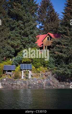 Scenic view of a log home powered by solar panels in Anton Larsen Bay, Kodiak Island, Southwest Alaska, Summer - Stock Photo