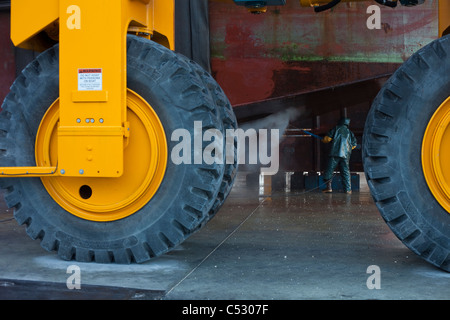 Looking past large tires on a Marine Travelift, a crew member washes boat hull, Kodiak Boat yard, Alaska - Stock Photo