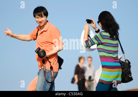 Asian international tourists or students taking photographs of each other - Stock Photo