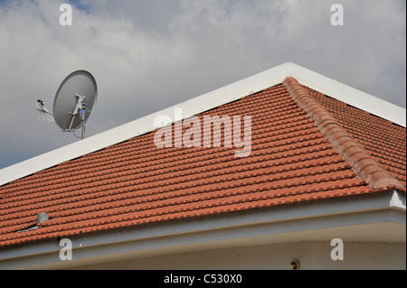 roof of a house with a satellite dish - Stock Photo