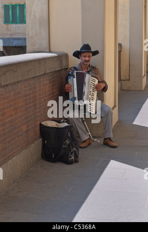 Male accordion street musician wearing black cowboy hat playing near the Ponte Vecchio bridge in Florence, Italy. - Stock Photo