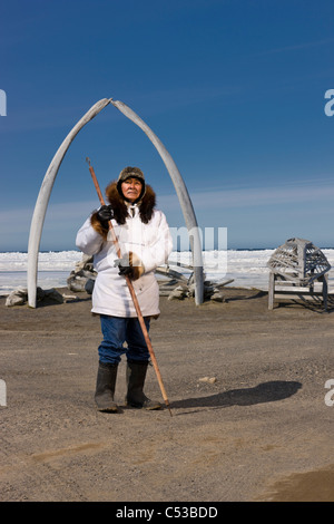 Male Inupiaq Eskimo hunter wearing his Eskimo parka , standing in front of a Bowhead whale bone arch and Umiaqs, - Stock Photo