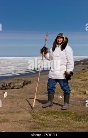 Inupiaq Eskimo holding a walking stick at Old Utkeagvik original town site overlooking the Chukchi Sea, Barrow, - Stock Photo