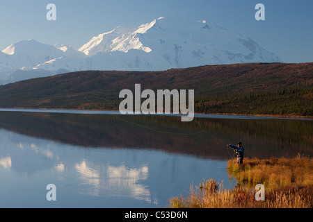 Fly fisherman casting over Wonder lake with Mt. McKinley in the background, Denali National Park and Preserve, Alaska - Stock Photo