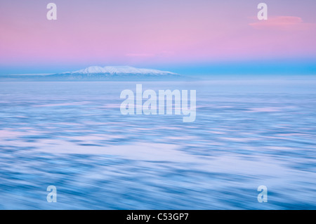 Blurred motion view of outgoing tide and ice at sunrise with Mt. Susitna in the background, Point Woronzof, Anchorage, - Stock Photo