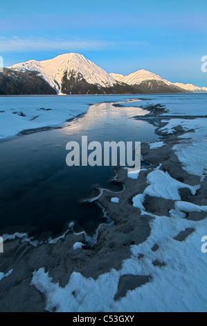 Morning light on the Kenai Mountains reflects on the waters and ice of Turnagain Arm, Southcentral Alaska, Winter. - Stock Photo
