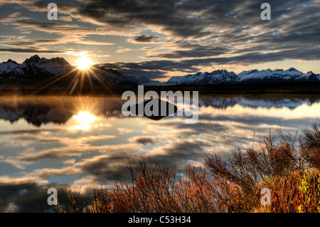 Sun rises over the Chugach Mountains with a pond and beaver lodge in the foreground, Chugach National Forest, Alaska - Stock Photo