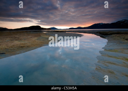 Evening sky reflects on the incoming tide at Harntey Bay near Cordova, Chugach National Forest, Southcentral Alaska, - Stock Photo