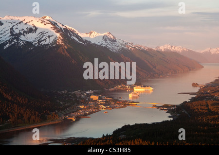 Aerial view of downtown Juneau and harbor at sunset with two cruise ships in port, Southeast Alaska, Summer - Stock Photo