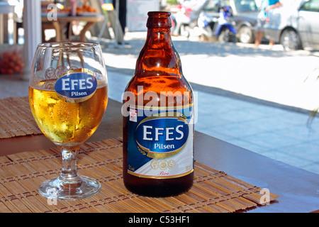Efes Pilsen Beer Bottle and Glass on restaurant Table in Side, Turkey - Stock Photo