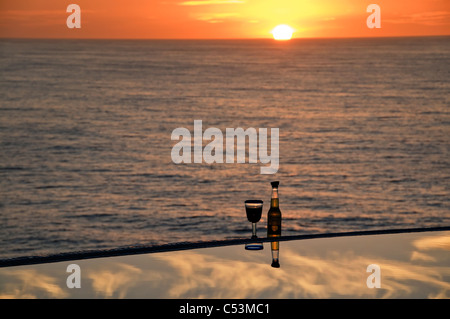 A glass of wine and a bottle of beer are placed on the edge of an infinity pool at sunset overlooking the Pacific - Stock Photo