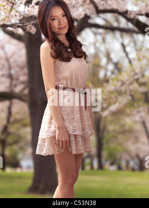Young smiling Asian woman in a beige summer dress standing under blooming cherry trees in a park - Stock Photo