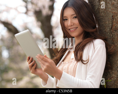 Young smiling Asian woman with a tablet computer in a park under a cherry tree - Stock Photo