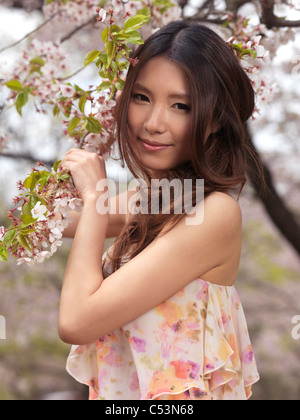 Portrait of a beautiful young smiling Asian woman standing at a blooming cherry tree in a park - Stock Photo