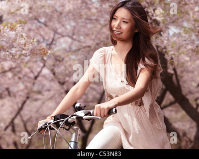 Young smiling Asian woman riding a bicycle in a park past blooming cherry trees - Stock Photo