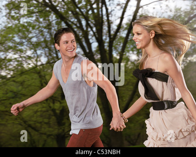 Young happy romantic couple running together holding their hands - Stock Photo